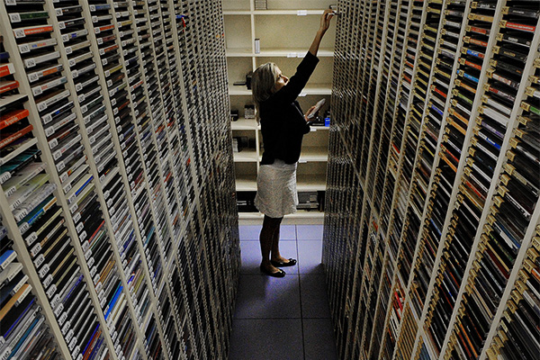 Woman struggles to find a CD, in room full of tall CD storage racks.